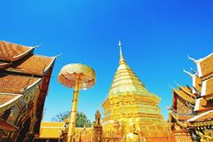 Big golden pagoda, umbrella and buddha statue with clear blue sky backgound at wat Phra That Doi Suthep Chiangmai, Thailand. Royalty Free Stock Photography