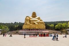 Big golden statue of Buddha in Qianfo Shan, Jinan, China. Jinan, China, April 2015 - Tourists walk in front if the Big golden statue of Buddha in Qianfo Shan Stock Photo