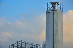 Big grain-silo in a cloudy sky. Industrial equipment from a bakery Stock Photos