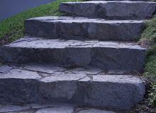 Big Gray Stone Stairs. Stairs made of large gray stones and mud surrounded by grass Stock Photos