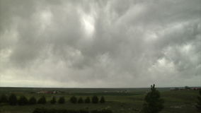 Big gray storm clouds over vast green land stock footage