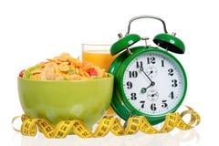 Big green alarm clock with breakfast Stock Images