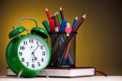 Big green alarm clock with notepad, black holder and pencils Royalty Free Stock Images