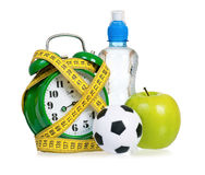 Big green alarm clock with small balls and bottle of water Royalty Free Stock Photos
