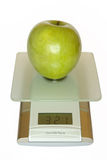 Big green apple on electronic. Kitchen scales Stock Photos