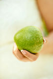 The big green apple in female hands Royalty Free Stock Photos