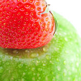 Big green apple with water drops and strawberries Stock Photos