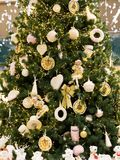 Big green Christmas tree with white and yellow decoration. Golden toys on festive pine tree. Gifts concept. Christmas tree lights. Big green Christmas tree with royalty free stock photography