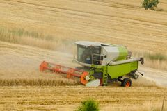 Big green combine harvester machine working in a wheat gold field, mows grass in summer field. Farm machinery harvesting grain in stock photos