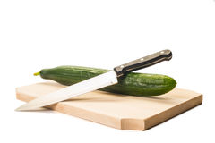 Big green cucumber and a cook knife on a wooden board Royalty Free Stock Photos