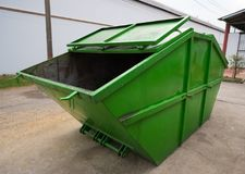 Big green dumpster garbage truck on the road in the factory, Side view.  stock photo
