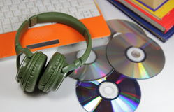Big green earphones  with disks and the computer Stock Photos