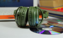 Big green earphones  with disks and the computer Stock Photography