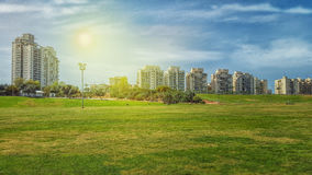 Big green field in front of residential buildings Stock Photos