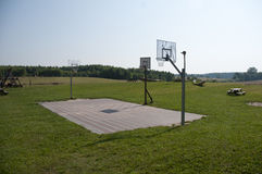 Big green flied have a basketball area. In summer camp Stock Image
