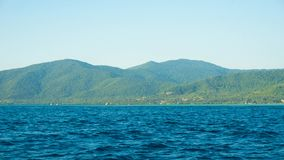 A big green island with deep blue dark sea in karimun jawa island royalty free stock image
