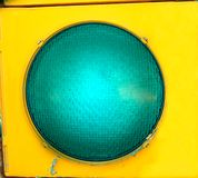 Big Green Light. Extra large green light glows inside the yellow signal light by intersection Stock Image