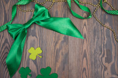 Big green satin bow, clover leaves and gold beads. Saint Patricks Day Royalty Free Stock Image