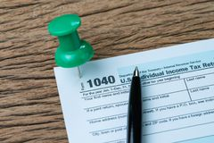 Big green thumbtack pin on 1040 individual income tax form with. Pen to fill in, reminder for yearly submission for US internal revenue service department stock photo