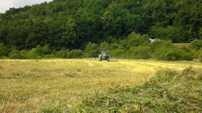 Big green tractor with haymaker working on the meadow in farmland. Haymaking in the countryside below hills Stock Photo