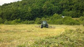 Big green tractor with haymaker working on the meadow in farmland. Haymaking in the countryside below hills Stock Images