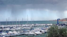 Big grey cloud on the sea in yacht club. Huge rainy cloud in yacht club in the mediterrenian sea at orihuela costa, alicante, spain stock footage