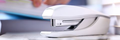 Big grey stapler stand at clipboard pad with clerk arms. And pile of papers in background closeup letterbox view royalty free stock photos