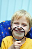 Big grin. Boy using magnifying glass to make a big grin royalty free stock photos