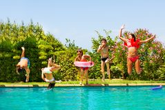 Kids playing pool games during backyard party. Big group of age-diverse boys and girls playing pool games, jumping into water during backyard party royalty free stock image