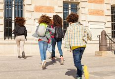 Big group of kids with backpacks running to school. Big group of boys and girls with backpacks running to school at sunny day Royalty Free Stock Images