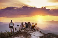 Big group friends mountain top sunset. Big group of friends stands on mountain top and looks at beautiful sunset. Travel with friends concept stock images