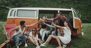 Big group of friends at the picnic party drinking beer and cheers, sitting behind of a retro van.  stock footage