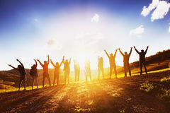 Big group of friends raising arms on sunset together. Big group of happy friends stands on sunset backdrop with raised arms together. Friendship or teamwork Stock Images