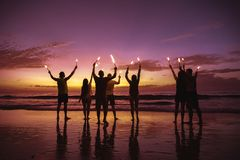 Big group friends with sparkle lights at beach stock images