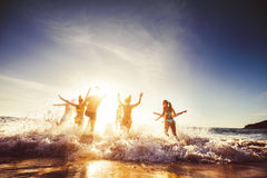 Big group friends sun beach travel. Big group of friends runs in sun light at the beach into the sea. Travel concept. Space for text Stock Photography
