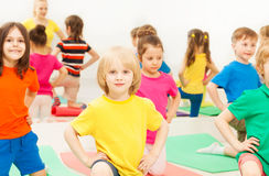 Big group of happy kids kneeling during gymnastics. Big group of happy kids kneeling with their hands on waist, during gymnastics in sports club Stock Photos