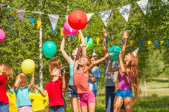 Big group of happy kids playing balloons outdoor Stock Photos