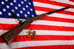 Big Gun on American Flag. A Quigley Sharps 45-170 Caliber Big Gun Rifle and a few bullets laying on an American flag.  Shallow depth of field Royalty Free Stock Photography