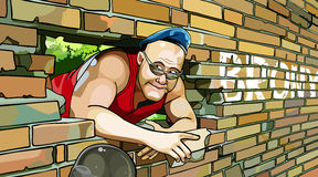 Big guy in the blue beret looks out of a broken brick wall Royalty Free Stock Photo