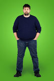 Big guy in full in front of green screen. Complete body shot of a big guy looking at camera, real ordinary middle age bearded white man with weight problem in Royalty Free Stock Photography