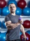 Big guy holding ridiculously small dumbbells stock photos