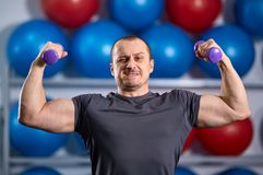 Big guy holding ridiculously small dumbbells Stock Photo