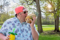 Big guy pretending to take a big bite of a pineapple. Big guy pretends to take big bite out of a pineapple stock images