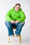 Big guy sitting on a chiar Stock Photos