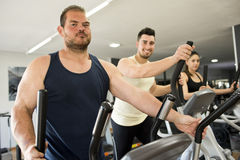 Big guy training in elliptical bike Royalty Free Stock Photos