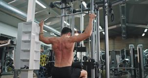 Big gym class athletic guy exercises hard doing exercises for his back muscle and triceps lifting up the weights.  stock footage