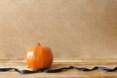 Big Halloween pumpkin decorated with black ribbon stock photography