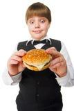 Big hamburger. Fun young fat schoolboy eating big hamburger Royalty Free Stock Photo