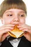 Big hamburger. Young fat schoolboy eating a big hamburger Stock Image