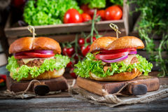 Big hamburger with beef and cheese. On old wooden table Royalty Free Stock Images
